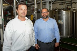 Two Certified Public Accountants stand in industrial warehouse full of equipment