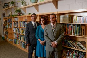 Three accountants standing in a library