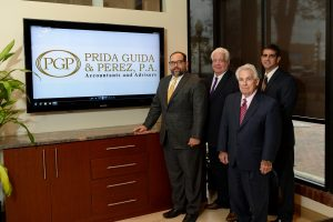 Prida Guida and Perez Professional Accountants stand in front of new logo replacig Prida Guida and Company